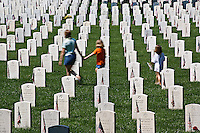 Young family walking through cemetery and American flags on tombs of American Veterans on Memorial Day, Zachary Taylor National Cemetery, Louisville, Kentucky.On National Register of Historic Places