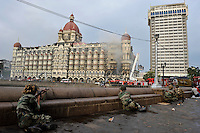 Indian soldiers takes cover behind a sea wall while The Taj Mahal hotel burn during the final gun battle between the Indian commandos and  militants inside the hotel in the early hours of 29th of November 2008 in Mumbai, India.