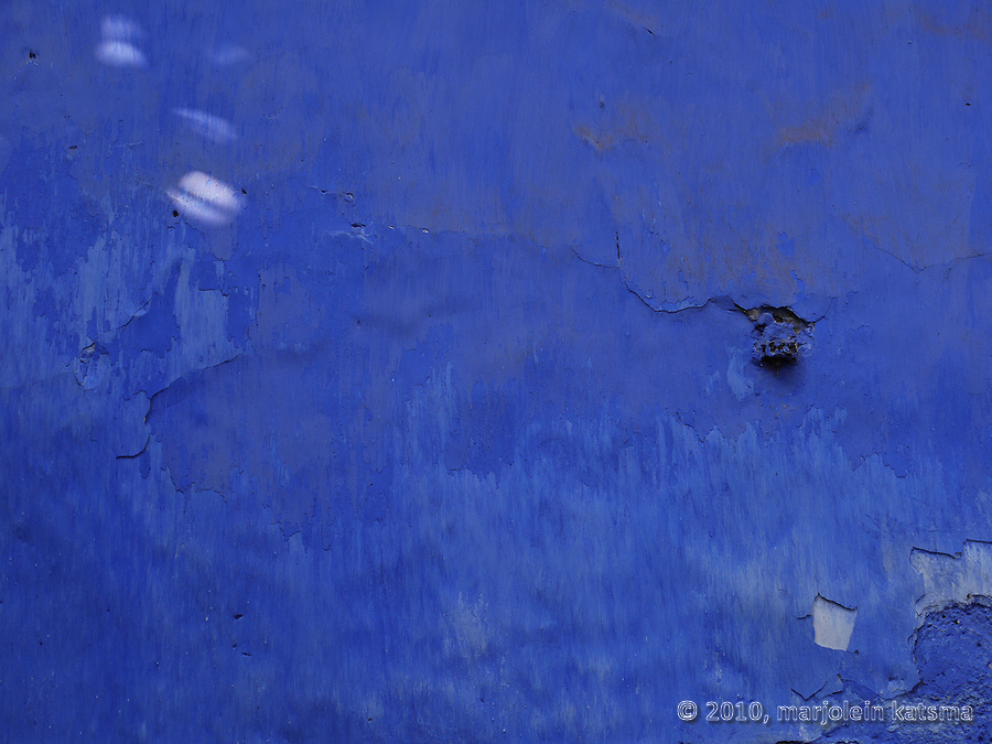 This bright blue wall in Panaji, Goa looks freshly-painted, but in the lower half the color is running a bit, as if it's a watercolor. The blue is such a bright color, that the bits of dust on the wall are actually contrastnig with it.