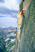 Rock climber on the face of Thank God Ledge on the North West face of Half Dome in Yosemite National Park, California with clouds and mountains in the distance.