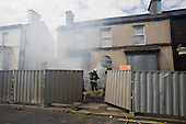 Firefighters use an empty house in Anfield, close to Liverpool football stadium, in a training exercise.   Many neighboruing streets are scheduled for demolition by the Merseyside NewHeartlands partnership, financed by the Housing Market Renewal Fund, part of a government strategy aimed at tackling 'low demand'.  Some long-standing residents oppose the demolition of their homes.