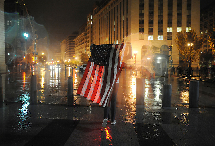 An election night reveler carries an American Flag away from a celebration at the White House after Barack Obama was voted president of the United States, November 4, 2008.