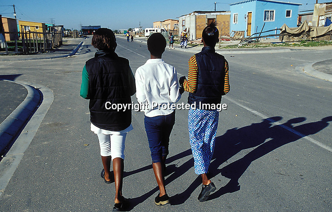LSTEENA30011.Lifestyle. Teenager. Young teenage girls walking down the street. RDP housing, relaxed, socialising. 99..©Per-Anders Pettersson/iAfrika Photos
