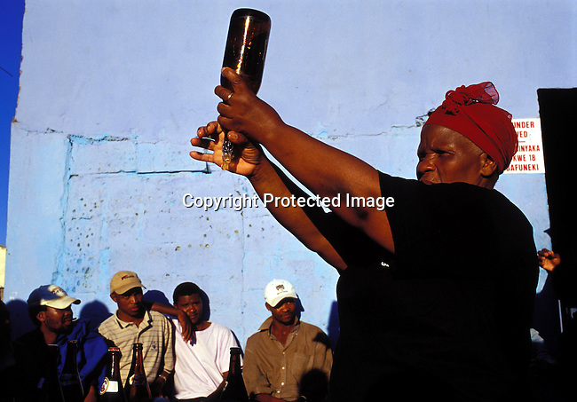 "dihealth00713.Digital. Health. Aids Awareness. Mama Avalon Mayiphela, and HIV-Aids worker, demonstrates how to use a condom for customers at a local bar on May 15, 2003 in George, South Africa. The project is called ""Amy's tavern Aids and Condom demonstration"", a project run by the Amy Biehl foundation. Amy was killed in a pre-election attack in Guguletu, Cape Town in 1993. Three of Amy's convicted killers were pardoned during the TRC hearings and Linda Biehl, her mother, later started the Amy Biehl foundation and Linda employed two of the killers. Social issues. .©Per-Anders Pettersson/iAfrika Photos."