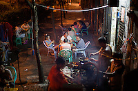 People eat at a nameless shaokao restaurant on the sidewalk near the west gate of the Ciqikou area of Shapingba district in Chongqing, China. Ciqikou's ancient town is a major tourist destination in Chongqing, but at night, the tourists disappear and locals come out to eat from street food vendors in the area.<br /> <br /> The restaurant is run by Liu Pang Wa, whose wife and two children also help. Most of the customers there are neighborhood locals, and the restaurant stays open until 3 or 4 am. Liu Pang Wa said his specialties are eggplant, pig brain, and fish. The area is close to western banks of the Jialing River in northwestern Chongqing city.