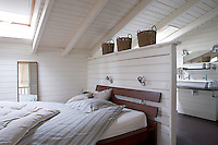 A partition which doubles as a headboard separates the wooden bed from the ensuite bathroom in this wood-clad attic bedroom