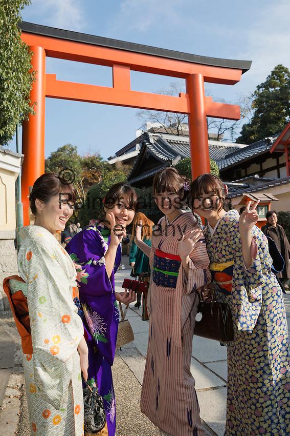 Japan, West Honshu, Kansai, Kyoto: Young Japanese girls below torii gate in traditional kimonos at Yasaka Shrine | Japan, West-Honshu, Kansai, Kyoto: junge japanische Frauen im traditionellen Kimono vor dem Torii zum Yasaka Tempel