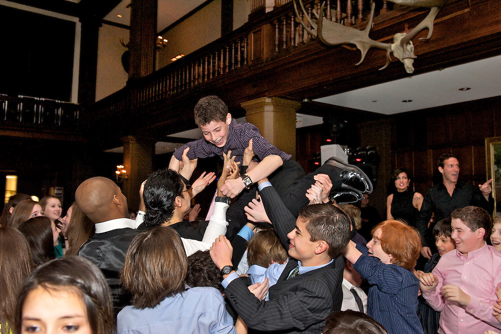 Bar Mitzvah boy being lifted in the air during the horah.