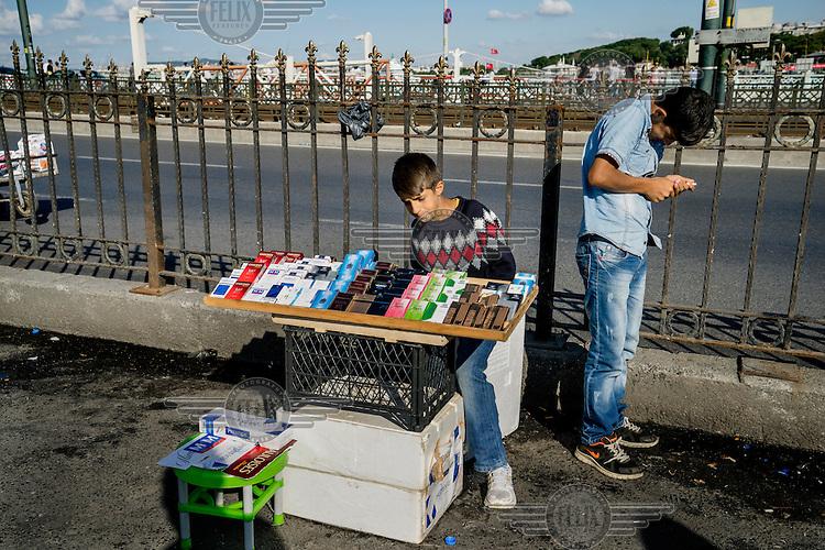A pavement cigarette vendor sells cheap cigarettes on the Galata Bridge.