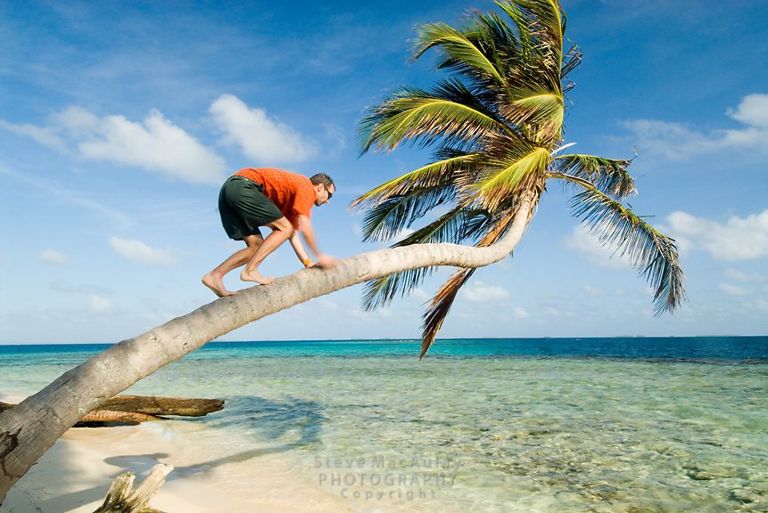 Man in orange shirt and green shorts playing around on tropical island beach, Comarca De Kuna Yala, San Blas Islands, Panama