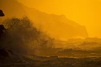 Kee sunset with wave crashing against cliffs, Haena, KauaI