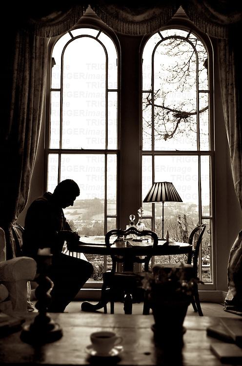 A middle aged male figure in an elegant sitting room with antique furniture beside a large window reading a newspaper