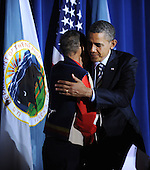 """President Barack Obama hugs Hartford Black Eagle, his Crow nation """"father"""" who """"adopted"""" him during the 2008 campaign, after speaking at the White House Tribal Nations Conference at the U.S. Department of the Interior December 2, 2011 in Washington, DC. The purpose of the conference is to continue to strengthening the government-to-government relationship between the United States and tribal governments..Credit: Olivier Douliery / Pool via CNP"""