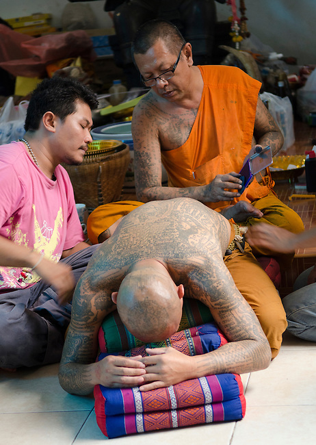 Nakorn Chai Sri, Thailand, March 2, 2012, Wat Bang Phra Buddhist Monk prepares to stamp a sak yant magical tattoo pattern on a devotee in preparation.