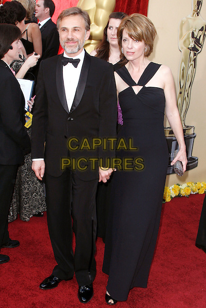 HRISTOPH WALTZ & GUEST.The 82nd Annual Academy Awards held aat The Kodak Theatre in Hollywood, California, USA..March 7th, 2010.oscars full length black dress tuxedo .CAP/EAST.©Eastman/Capital Pictures.