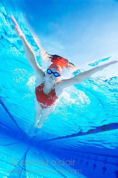 Young woman with red swim suit swimming laps, breaststroke, in pool in Coral Springs, Florida.  Underwater view.
