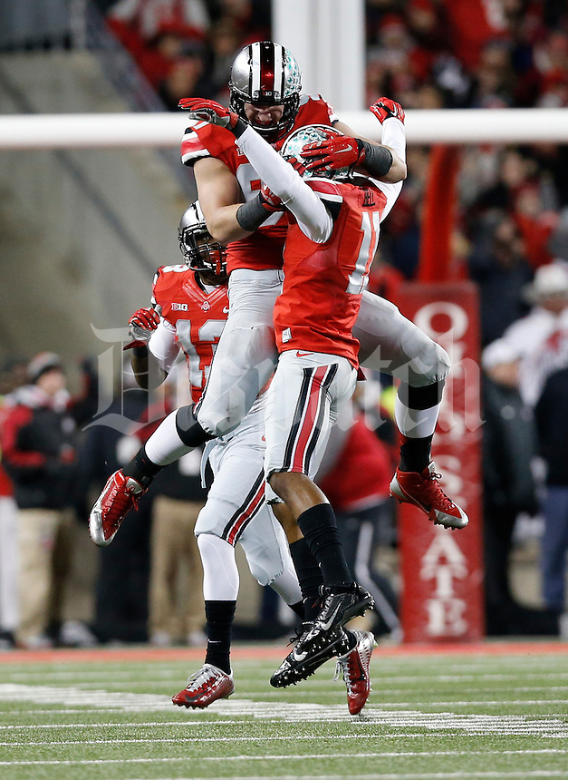 Ohio State Buckeyes defensive lineman Joey Bosa (97) leaps to congratulate defensive back Vonn Bell (11) after he recovered a fumble during the first quarter of the NCAA football game at Ohio Stadium on Nov. 1, 2014. (Adam Cairns / The Columbus Dispatch)