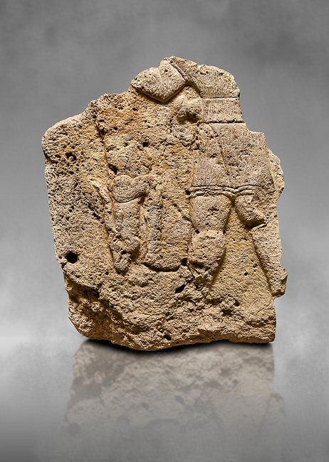 Hittite relief sculpted orthostat stone panel of Long Wall Limestone, Karkamıs, (Kargamıs), Carchemish (Karkemish), 900 - 700 B.C. Anatolian Civilisations Museum, Ankara, Turkey. The short-skirted figure with a dagger at the waist holds the gazelle from its hind legs.<br /> <br /> On a grey art background.