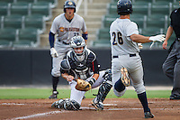 Kannapolis Intimidators catcher Brett Austin (10) prepares to apply the tag to Mike Ford (26) of the Charleston RiverDogs as he tries to score a run at CMC-NorthEast Stadium on June 27, 2014 in Kannapolis, North Carolina.  The Intimidators defeated the RiverDogs 6-5.  (Brian Westerholt/Four Seam Images)