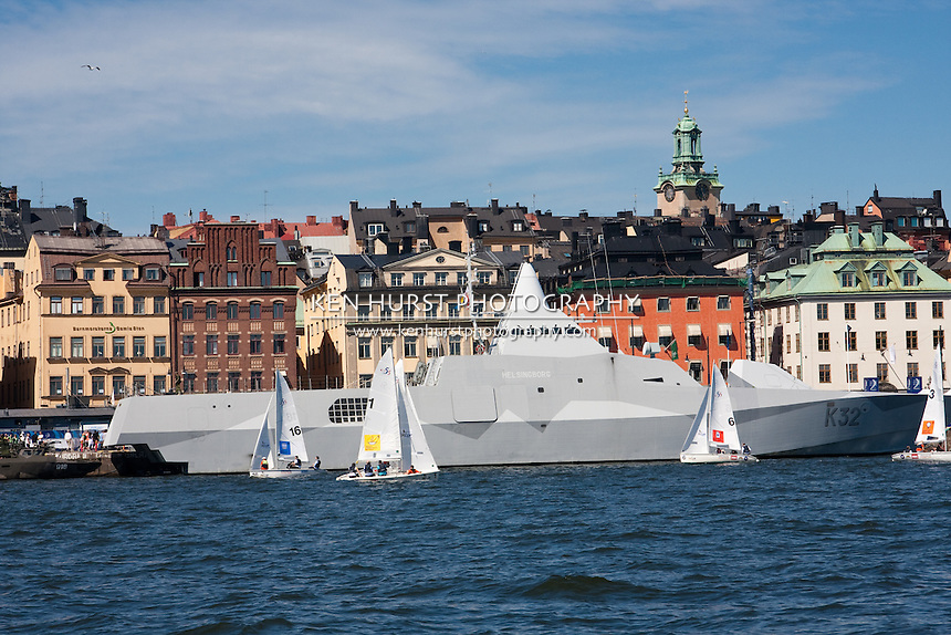 Sailboats in the harbor with scenic views of the city of Stockholm, Sweden  and the HMS Helsingborg, a modern Visby class corvette of the Swedish Navy in the background.
