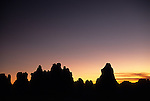 A colorful sunset sky silhouettes the hoodoos of the Needles District in Canyonlands National Park, Utah.