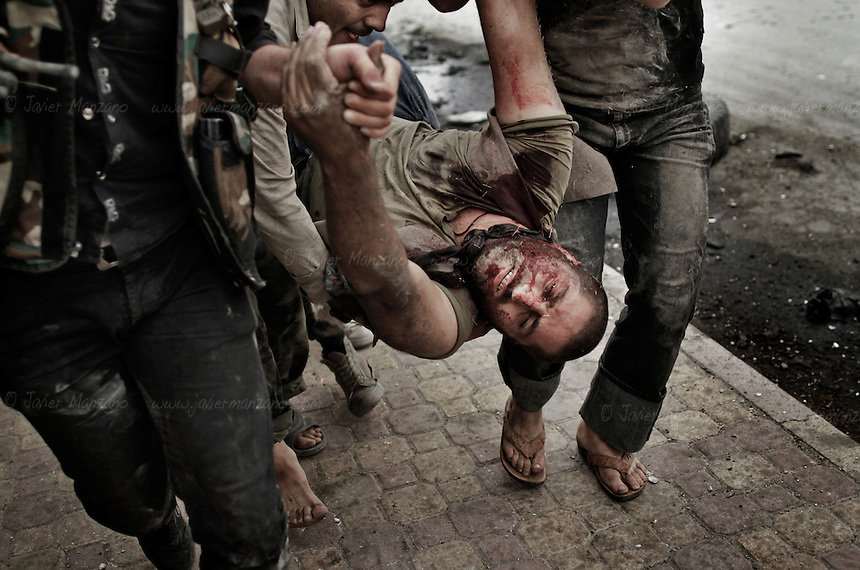 Members of the Al-Baraa Bin Malek Katiba, a part of the Free Syria Army under the Al-Fatah brigade, attempt to rescue a man who was shot by a sniper positioned in a building across the street on a main road that crosses the Bustan Al-Bashar district of Aleppo on October 20, 2012. Several vehicles drove past this man as he looked up in desperation (no one stopped because of the risk of being shot by the sniper). At a moment's notice, the man stood up and began to run towards the members of the Free Syria Army. As he approached the other side of the street, he was shot a second time, falling to the ground. Free Syria Army soldiers crawled through the ground to reach him and pulled them towards a vehicle that rushed him to the hospital. It is not known if he survived. Three civilians were shot on this main road in the space of three hours by the same sniper. ..© Javier Manzano.