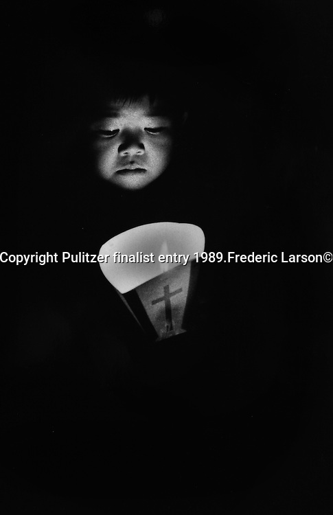 A child hold a candle during a annual memorial march held in Nagasaki Japan for the souls who lost their life in the A-bomb explosion in 1945. Pulitzer finalist entry 1989 Frederic Larson©