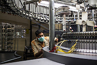 Workers tend to the machines in the Knitting area of the Pratibha vertically integrated garment unit in Indore, Madhya Pradesh, India on 11 November 2014. Photo by Suzanne Lee for Fairtrade