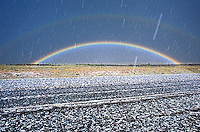 Display of primary and secondary rainbows while hailstorm is in progress along highway in the highlands of northeastern New Mexico.