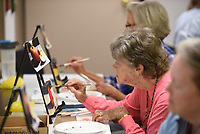 NWA Democrat-Gazette/DAVID GOTTSCHALK Laura Raney leans in Monday, October 7, 2019, to continue to paint her apple during the Oil Painting for Beginners - Still life class at the Northwest Arkansas Fab Lab in Fayetteville. The class, offered by the University of Arkansas Osher Lifelong Learning Institute, is a hands-on workshop designed to bring painter through the  of still life oil painting from a blank canvas to a finished work. The class was taught by Helen Eaton and Julie Brandt.