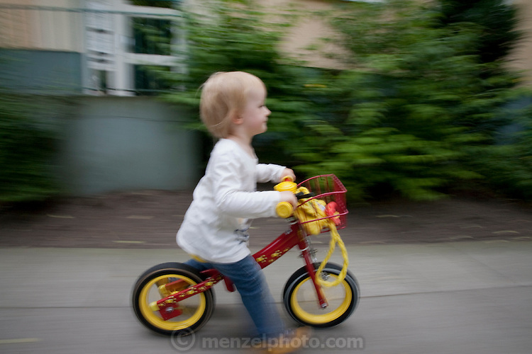 Lillith Sturm, 2 1/2 riding her bike in front of their apartment. The family was photographed for the Hungry Planet: What I Eat project with a week's worth of food in June. Model Released.