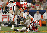Ohio State's Simon Fraser, 75, and teammate Bobby Carpenter, 42, team up to stop Oklahoma's Prentiss Elliott, 11, in the second half of their game at the Alamdome December 29, 2004. (Dispatch photo by Neal C. Lauron)  ALAMO BOWL .