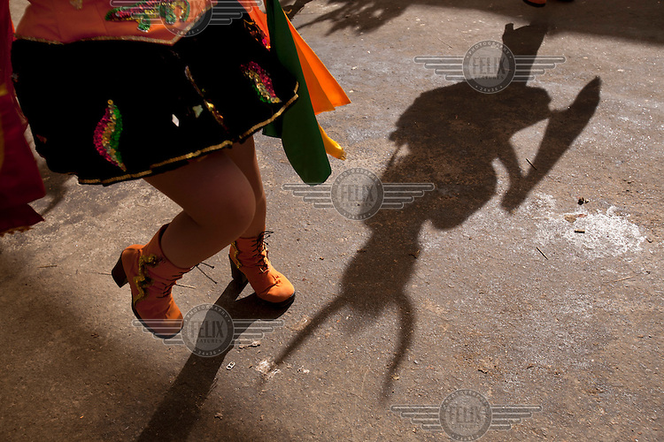 A woman dances at the Carnaval de Oruro. During the fiesta many people sacrifice llamas and give offerings such as coca leaves and cigarettes to show their dedication to the Devil, a Virgin, Pachamama or Mother Earth. The Devil (or Uncle) is a mythical character that protects the miners of Oruro who work in dangerous conditions hundreds of metres below the ground. During the carnival, people dress in outrageous costumes and dance for days before arriving at the Church of Socavon, where they pay their respects to a virgin. Ironically, many of the dancers wear devil costumes.