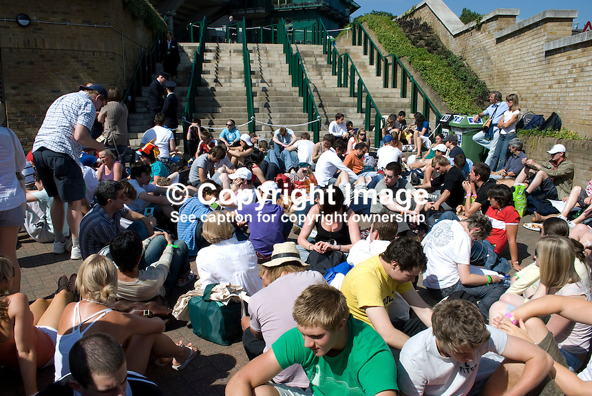 Tennis enthusiasts sit at the bottom of the steps waiting for admission to start at the Wimbledon Tennis Champtionships, London, UK. 200906232578..Copyright Image from Victor Patterson, 54 Dorchester Park, Belfast, UK, BT9 6RJ..Tel: +44 28 9066 1296.Mob: +44 7802 353836.Voicemail +44 20 8816 7153.Skype: victorpattersonbelfast.Email: victorpatterson@mac.com.Email: victorpatterson@ireland.com (back-up)..IMPORTANT: If you wish to use this image or any other of my images please go to www.victorpatterson.com and click on the Terms & Conditions. Then contact me by email or phone with the reference number(s) of the image(s) concerned.
