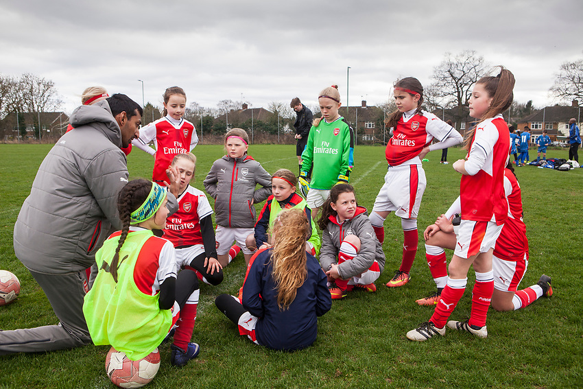 Acting Head Coach Rupen Shah, gives a talk to the girls during halftime. Arsenal Ladies Under 10 and AC Finchley boys team play a football game at Univeristy of Hertfordshire's campus sports village  football pitch in Hatfield.