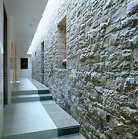 In this long corridor of a contemporary house in New Mexico the massive stone wall has been constructed from Telluride stone and the floors are a mixture of Portuguese and Spanish limestone