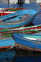 "Quaint fishing boats painted in a myriad of bright colors so they can be seen off the wild ""Green Coast"" of Northern Spain"