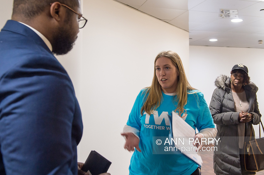 Melville, New York, USA. 24th January 2017. At center, TWWLI admin SUE MOLLER, of Merrick, speaks to, at left, GARRETT ARMWOOD, Long Island Regional Director for U.S. Senator Chuck Schumer of New York, as TWWLI member SHERRY MEDEROS looks on, when 15 members of Together We Will Long Island stop by Schumer's Melville office to share their concerns, especially about Trump's Cabinet appointees, #SwampCabinet. This Stop Trump Tuesday, #StopTrumpTuesday, event was part of nationwide political movement. They spoke in hall due to limited space. Members of organizations such as MoveOn, Indivisible, and TWW plan to visit their Senators' offices each Tuesday duringTrump's first 100 days of presidency.