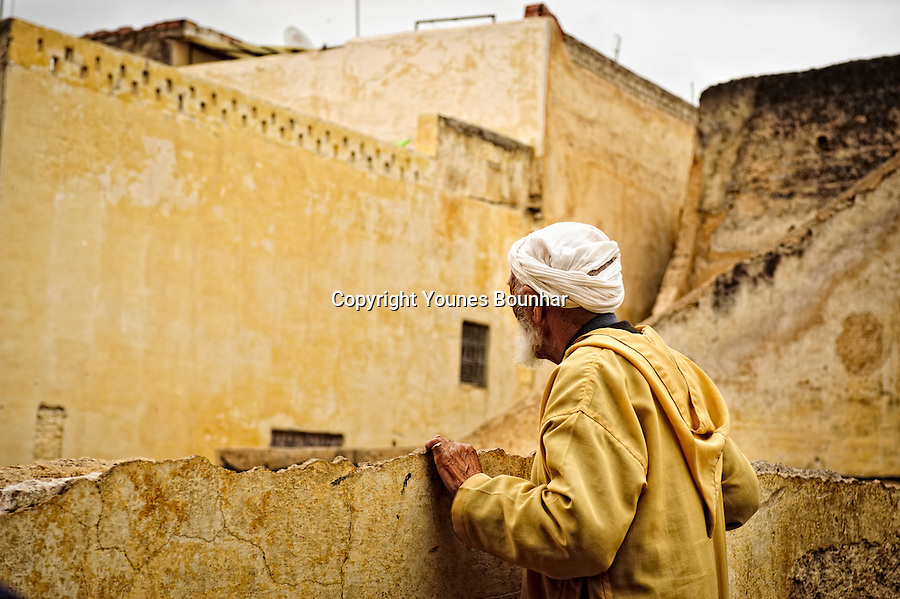 Old man looking over a bridge on Oued Fes separating the city in two.