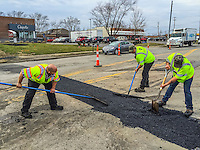 Construction workers smooth asphalt laid across a trench cut into the street during road construction.