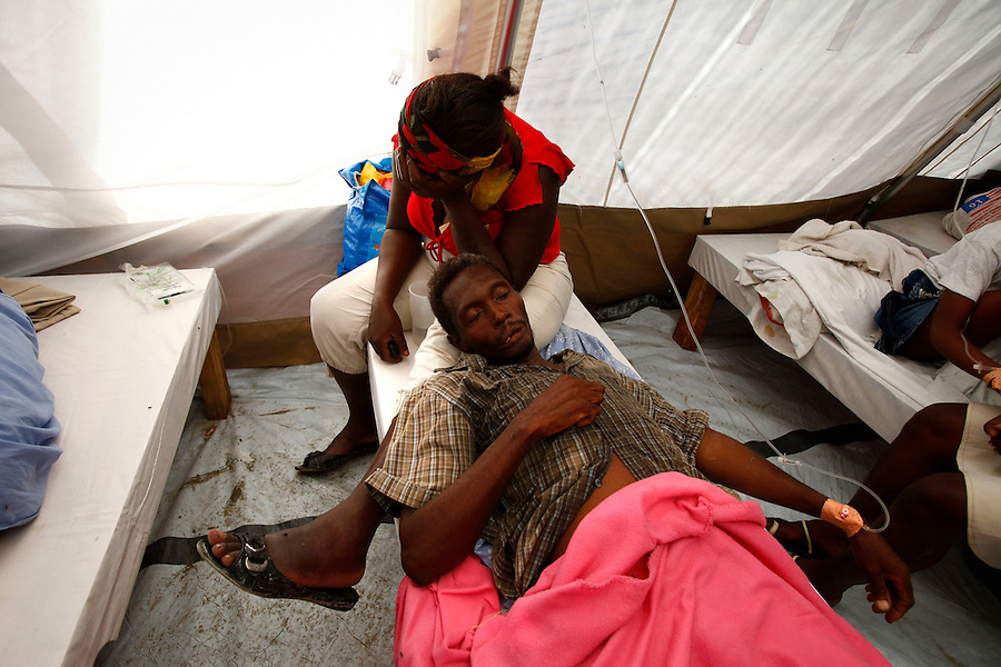 Nov 10, 2010 - Port-au-Prince, Haiti.A local resident looks after a family member suffering from cholera-like symptoms as he receives medical treatment in a small, crowded medical clinic set up in tents in the Cite Soleil area of Port-au-Prince, Haiti, Wednesday, November 10, 2010 as fears of a cholera outbreak spread through the area just two days after cases of the infection were confirmed in the area, the poorest slum in Haiti's capital. Officials from the Pan American Health Organization warn that Haiti's cholera epidemic, spread primarily through consuming infected water and food, is likely to grow much larger in the wake of Hurricane Tomas.  (Credit Image: Brian Blanco/ZUMA Press) 1