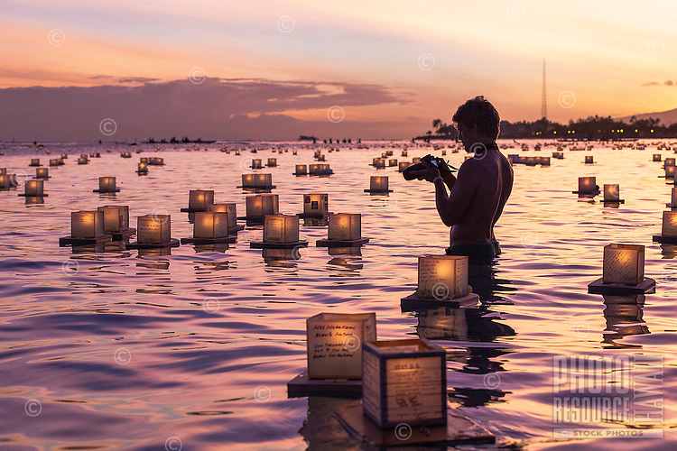 On Memorial Day at dusk, a man photographs lanterns floating on the ocean during the 15th Annual Lantern Floating Ceremony at Ala Moana Beach Park, Honolulu, O'ahu.
