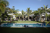 Manicured lawns surround the palm-fringed outdoor swimming pool of Lars Bolander's Palm Beach house