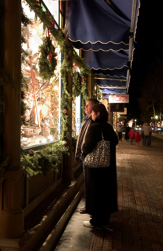 "Bob and Mary Samson enjoy afterhours window shopping on the Hyman pedestrian mall in Aspen, CO. ""We come to Aspen for Christmas, there's no other place like it,"" says Mrs. Samson. © Michael Brands."