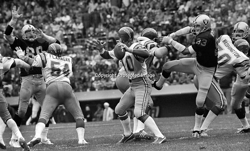 San Diego quarterback Bobby Douglas under pressure from Oakland Raiders Art Thoms and linebacker Ted Hendricks..(1975 photo/Ron Riesterer)