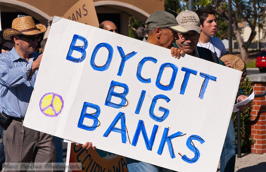 "Two men talk while holding a large ""Boycott Big Banks"" sign during the Occupy Orange County, Irvine march on November 5."