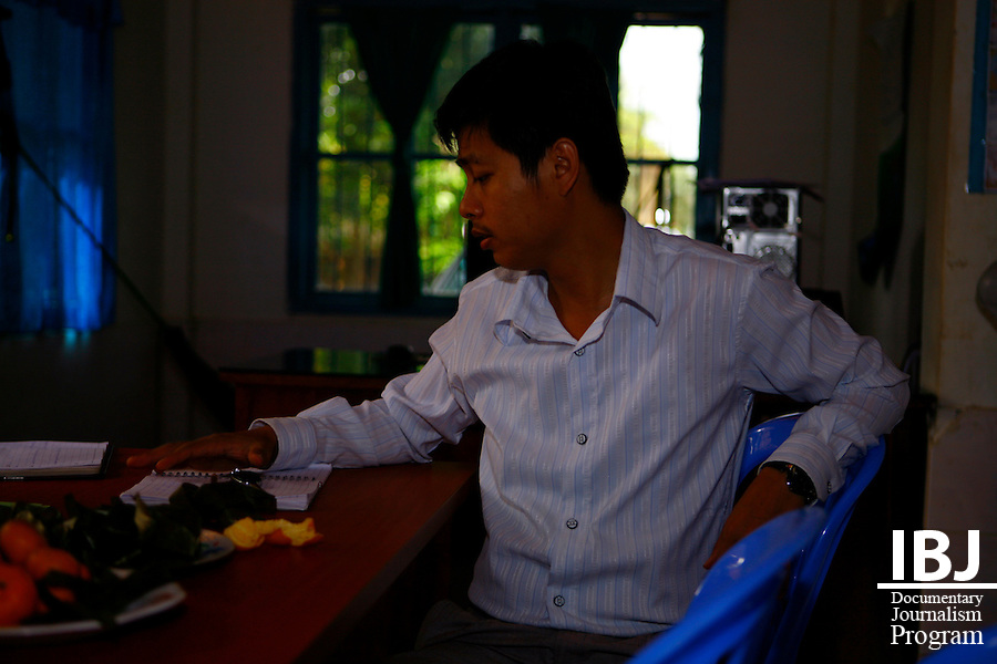 IBJ Lawyer Chhuonn Sithann looks over paperwork at IBJ office in Pursat.