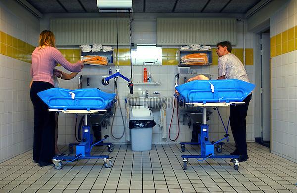 Gezondheidszorg, gehandicaptenzorg, met hulp van hoog-laag douche bed worden de verstandelijk en geestelijk gehandicapte bewoners gewassen in de vroege ochtend.