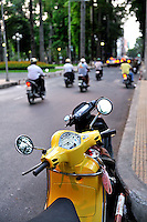 Yellow motorbike or scooter parked beside road filled with motorbikes, in late afternoon light. Ho Chi Minh City (Saigon), Vietnam