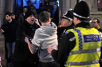 Pictured: A policeman breaks off people fighting in the early hours of New Year's Day. Sunday 01 January 2017<br />